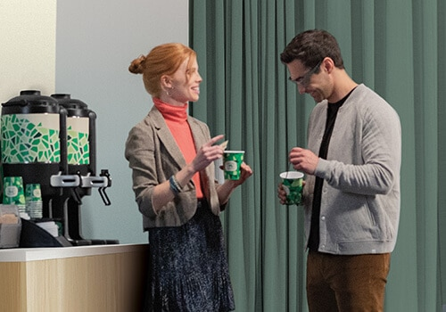 Two colleagues speak next to Chameleon self-serve coffee station