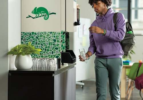Man pours cup of Chameleon Cold Brew from countertop solution