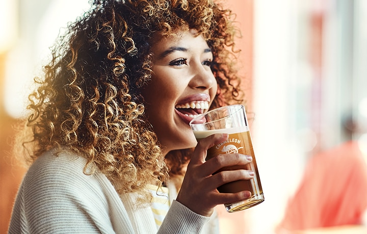 Laughing woman holds Chameleon Cold Brew