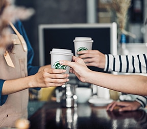 Barista serves Starbucks coffee at campus coffee shop
