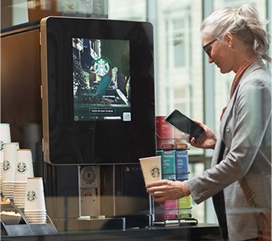 Woman uses touchless Starbucks Serenade brewer in apartment common area