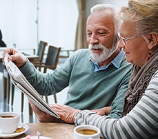 man and woman enjoy coffee in senior living facility