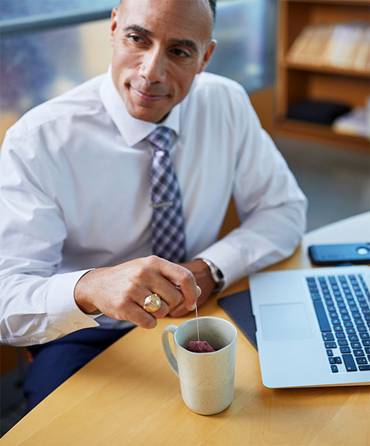 Man enjoying hot tea at work