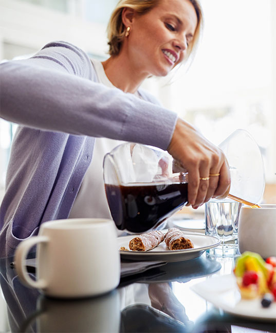 Woman pouring hot coffee at breakfast